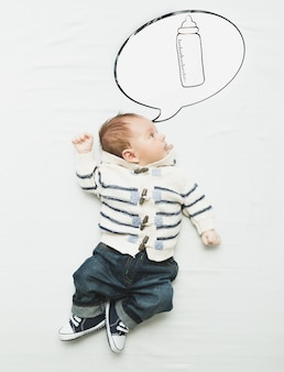 Cute little boy lying on bed and dreaming of bottle with milk