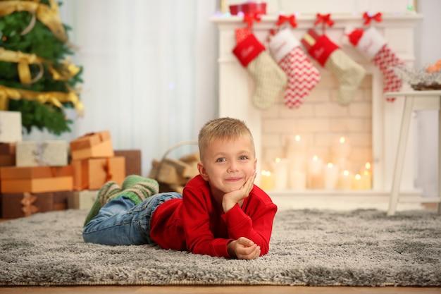 家でカーペットの上に横たわっているかわいい男の子