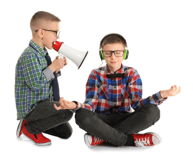 Cute little boy meditating and ignoring his friend with megaphone, on white