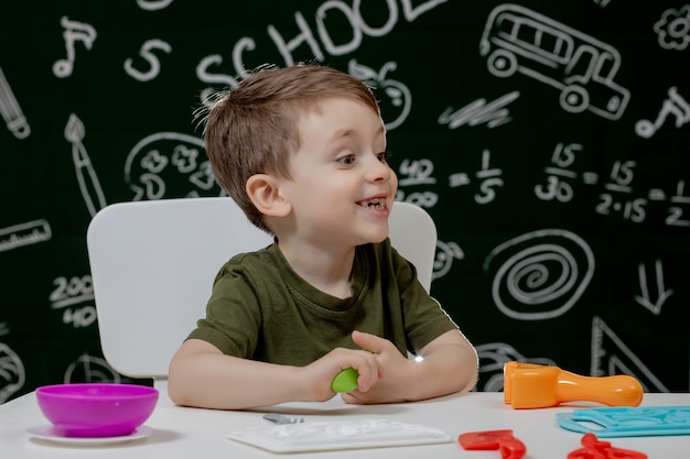 Cute little boy moulds from plasticine on table with a blackboard on a background. ready for school. home schooling. back to school