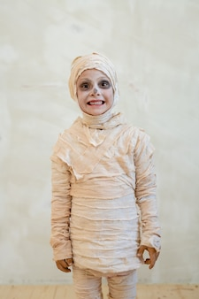 Cute little boy in mummy costume standing against white wall