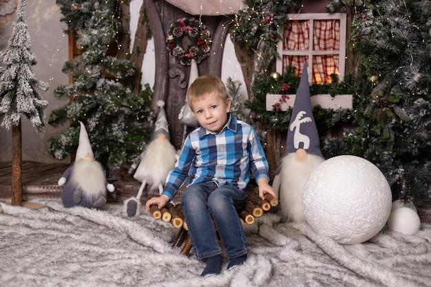 Милый маленький мальчик возле елки, игрушечного домика и гномов