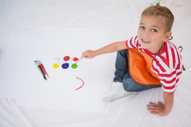 Cute little boy painting on floor in classroom at the nursery school
