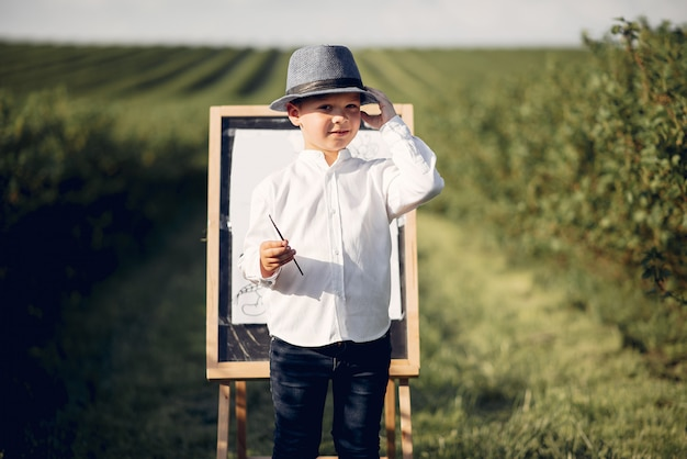 Cute little boy painting in a park