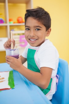 Cute little boy painting at table in classroom at the nursery school