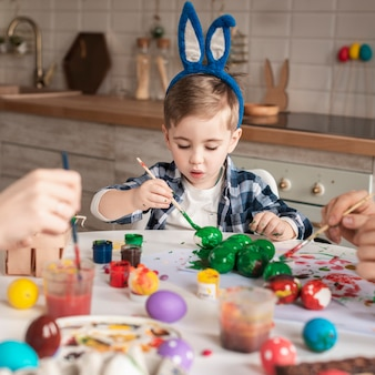 Cute little boy painting traditional eggs for easter