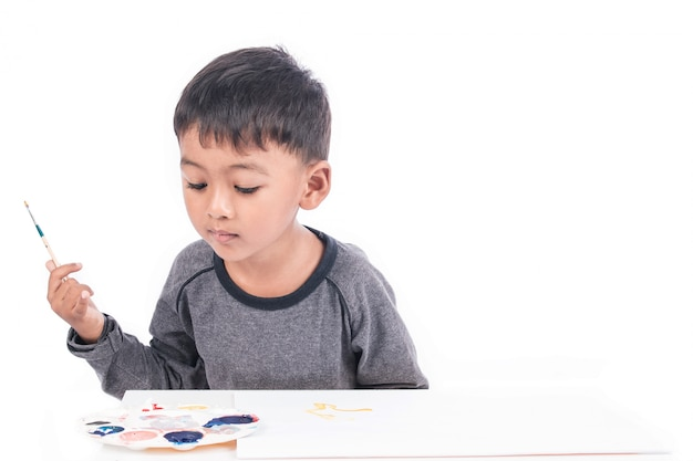 Cute little boy painting on white paper