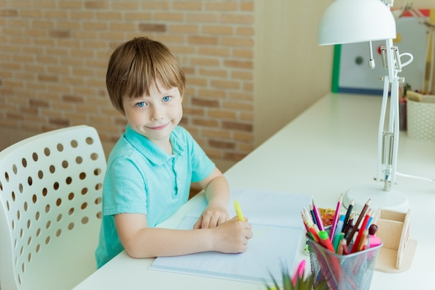 幼稚園や幼稚園で、自宅で色鉛筆で絵かわいい男の子。家にいる子供のためのクリエイティブゲーム