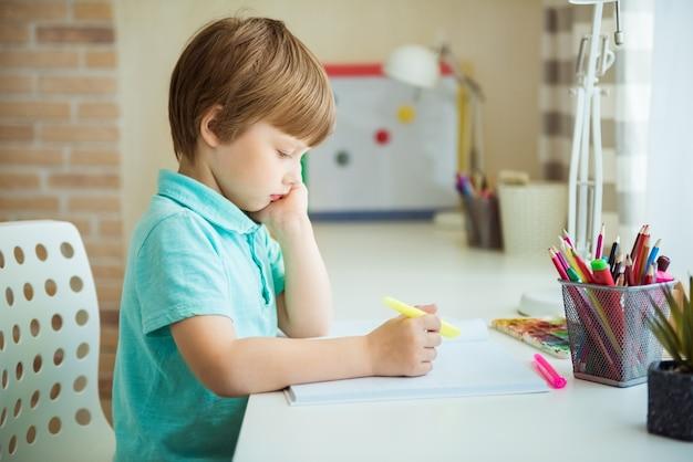 Милый маленький мальчик рисует цветными карандашами дома