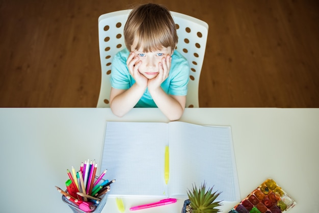 Cute little boy painting with color pencils at home, in kindergaten or preschool.