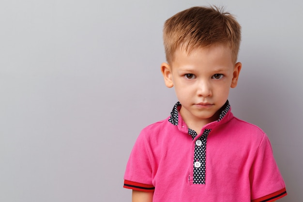 Cute little boy in pink t-shirt posing against grey background