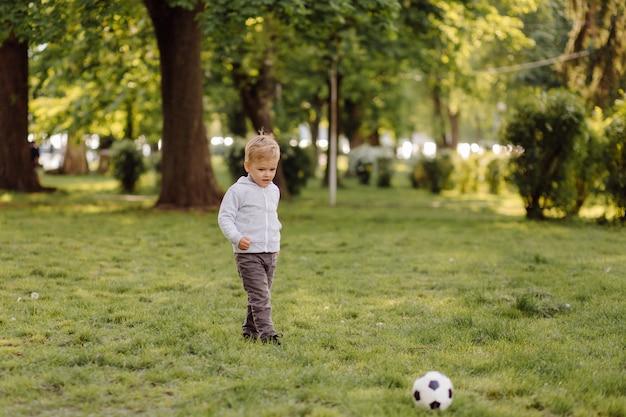 Милый маленький мальчик играть в футбол на открытом воздухе