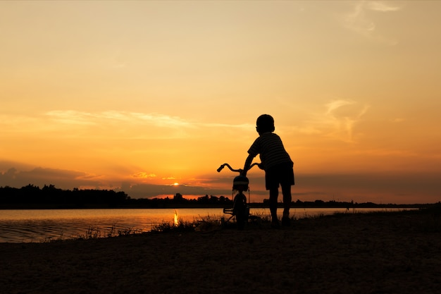 Cute little boy play and riding bicycle sunset background
