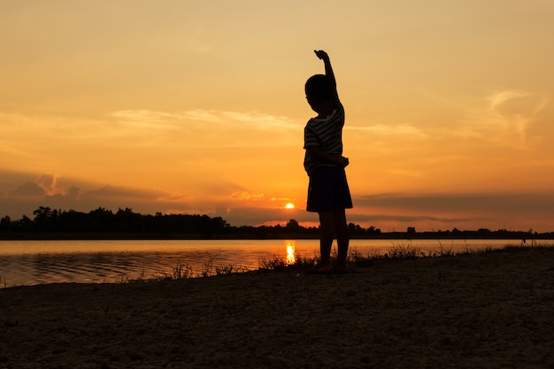 Cute little boy play at river sunset background