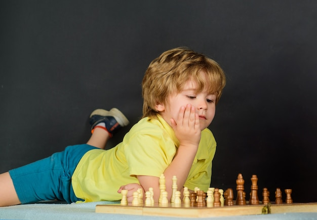 Cute little boy playing chess enjoying leisure time smart kid playing chess thinking how to make