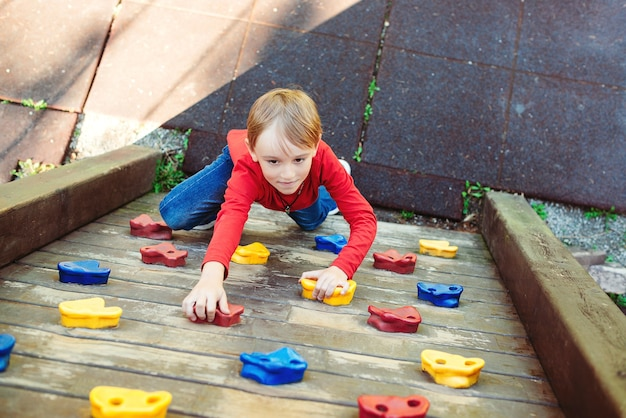 Cute little boy playing on the playground. happy child climbing on the wooden wall.