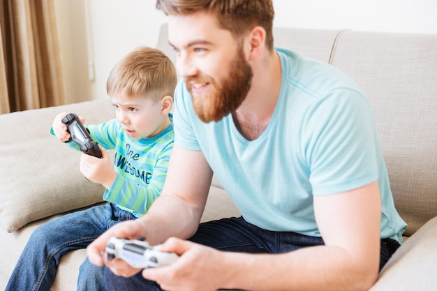 Cute little boy playing video games with his dad sitting on sofa at home