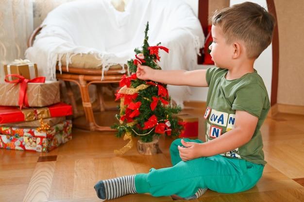Милый маленький мальчик играет с миниатюрной елкой