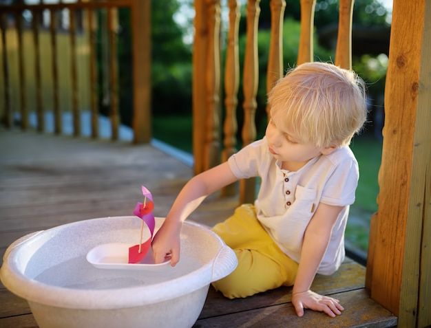Cute little boy playing with a homemade boat in a basin of water on the porch of a house. kids play.