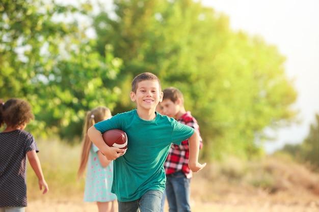 屋外でラグビー ボールで遊ぶかわいい男の子