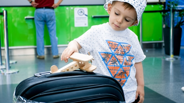 Cute little boy playing with toy airplane in airport before flight.