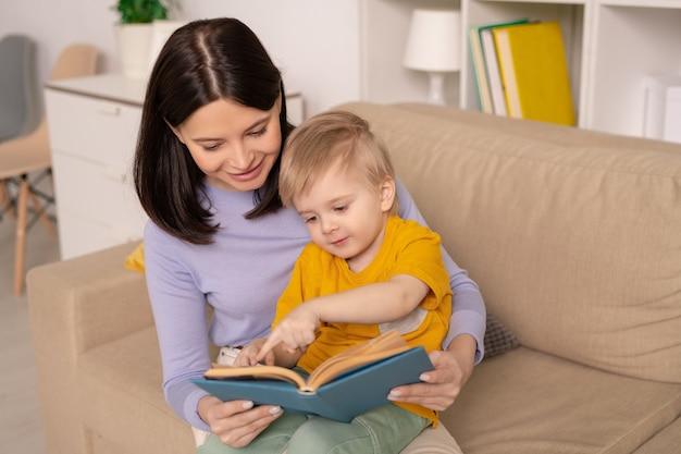Милый маленький мальчик, указывая на картинку на странице книги, обсуждая одну из сказок со своей матерью в период домашней изоляции