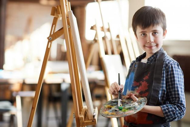 Cute little boy posing by easel