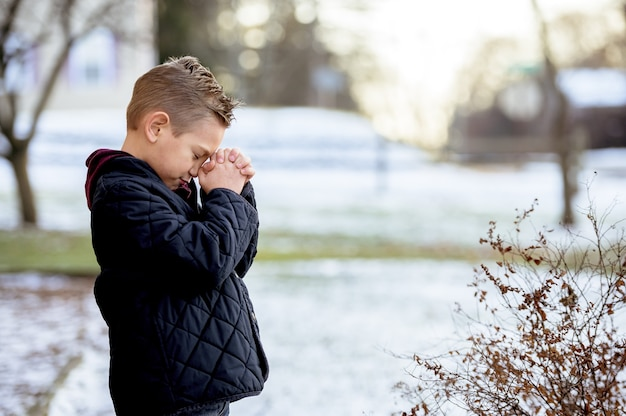 Cute little boy praying with closed eyes in the middle of the winter park