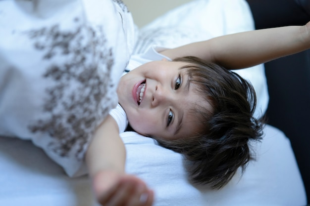 Cute little boy in pyjamas with smiling face lying in bed in the morning