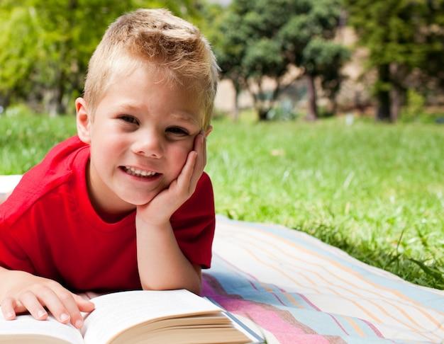 ピクニックで読書するかわいい少年