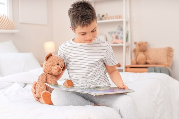 Милый маленький мальчик читает сказку на ночь дома