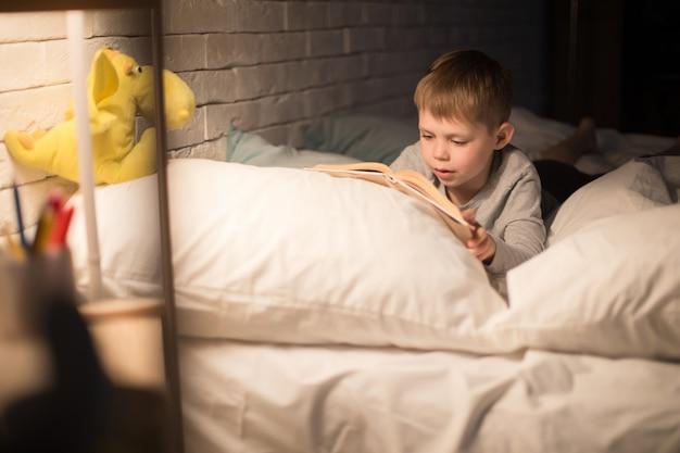 Милый маленький мальчик, читающий книгу ночью