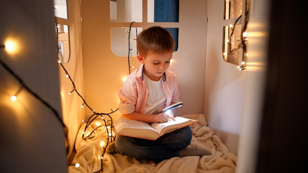 Cute little boy reading book with torch in his toy cardboard house at night. concept of child education and reading in dark room.