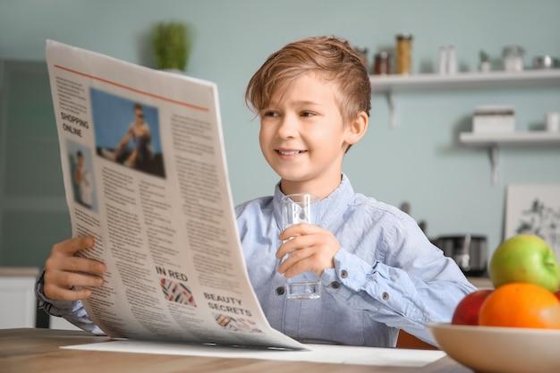 Милый маленький мальчик читает газету и пить воду на кухне