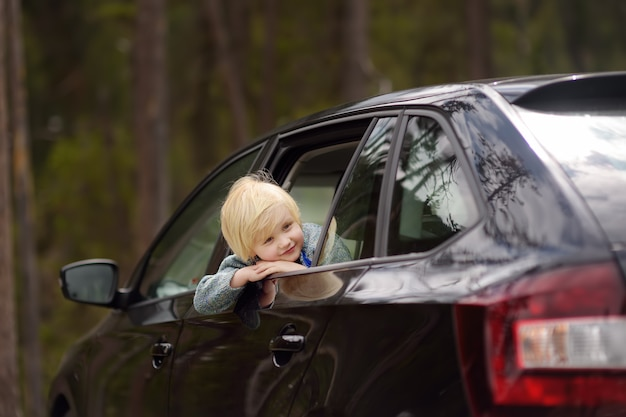 Cute little boy ready for a roadtrip or travel. family car travel with kids.