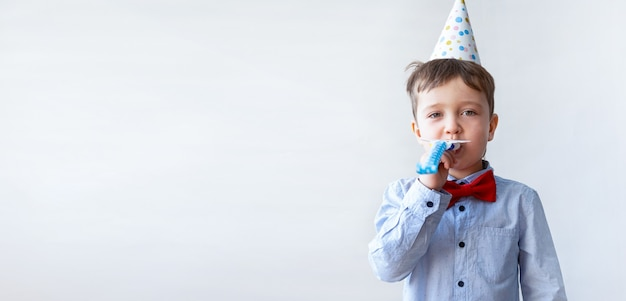 Cute little boy in red bowtie with party hat blow party horn. birthday party.