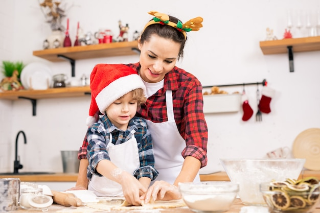 Cute little boy in santa cap and his mother in christmas headband making gingerbread cookies in the kitchen