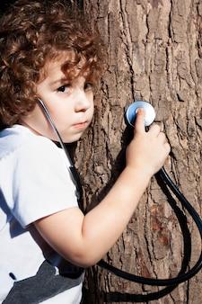 Милый маленький мальчик лепит ствол дерева с встревоженным лицом