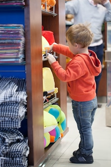 Симпатичный маленький мальчик, покупающий пляжные аксессуары