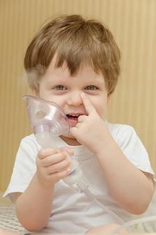 自宅のソファに座って、ネブライザー吸入器を介して呼吸しているかわいい男の子。その少年は咳吸入器を治す。