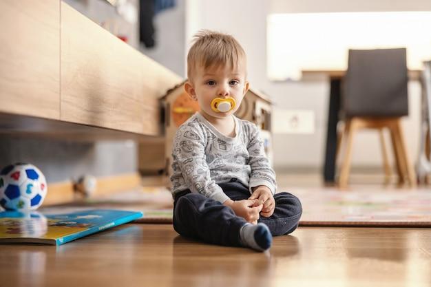 Милый маленький мальчик сидит дома с соской во рту.