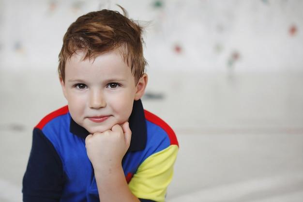 Милый маленький мальчик сидит в раздумье у скалолазания