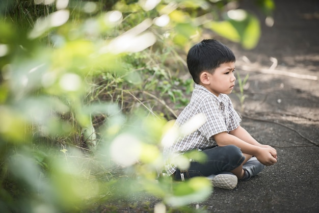 Cute little boy sitting on the ground in the summer park.