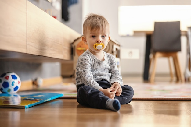 Cute little boy sitting at home with pacifier in his mouth.