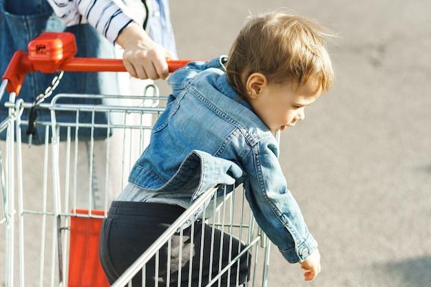 Милый маленький мальчик сидит в тележке для покупок