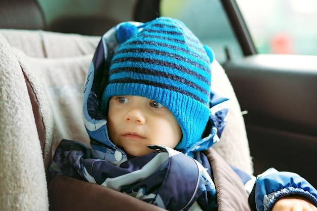 全体的に冬と帽子のイメージを身に着けている車のチャイルドシートに座っているかわいい男の子...