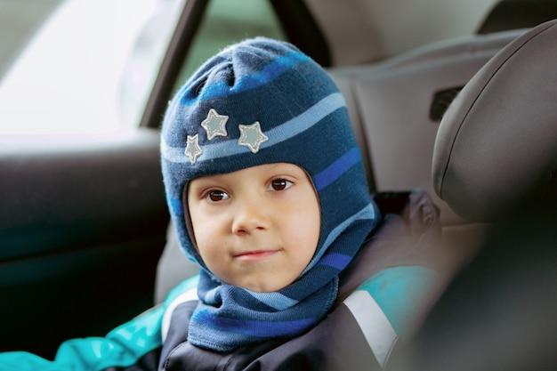 全体的に冬とフードハットのイメージを身に着けている車のチャイルドシートに座っているかわいい男の子...