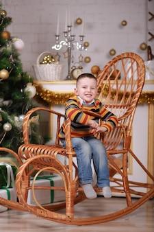 Милый маленький мальчик сидит в кресле-качалке возле елки.