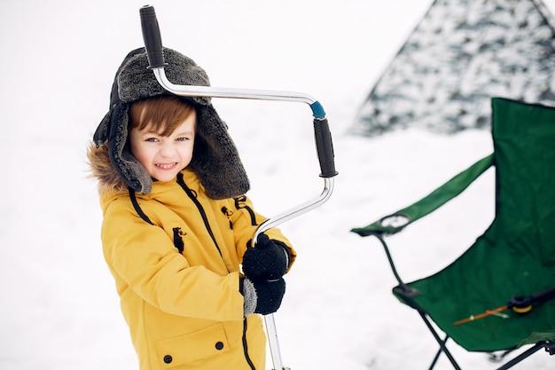 Милый маленький мальчик сидит на зимней рыбалке