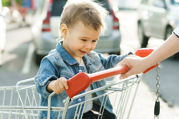 Cute little boy sitting in a shopping cart